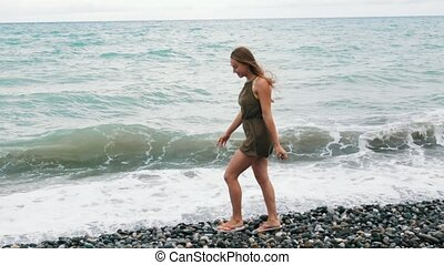 Young girl walking along the sea rocky coast. There are...