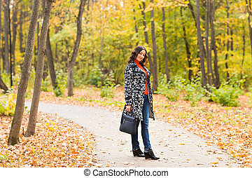 young girl walking in autumn park