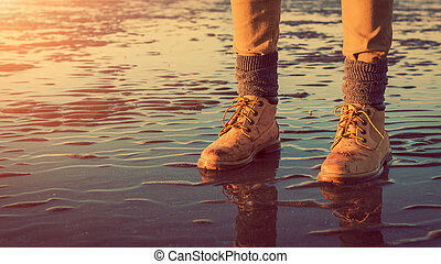 Young girl walking on a beach at low tide, feet detail, adventure concept