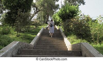 Young girl walking on stairs in tropical botanical garden. Batumi, Georgia