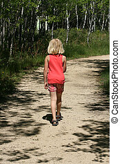 Young Girl Walking Through a Forest
