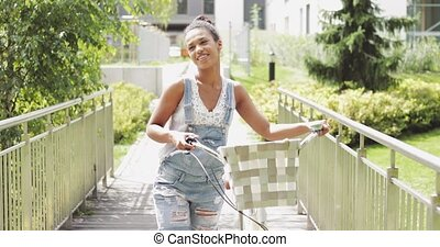 Young girl walking with bicycle - Beautiful young woman in...