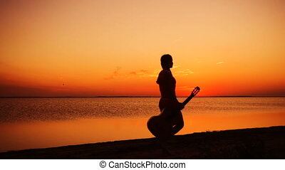 Young girl walking with guitar on the beach at sunset