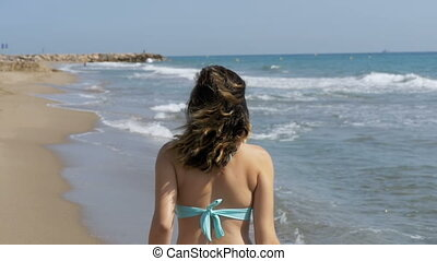 Young Girl Walks along the Beach of the Sea Coast in Slow...