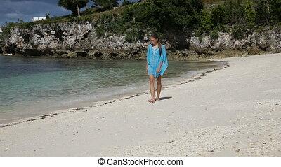 Young girl walks along the beach.