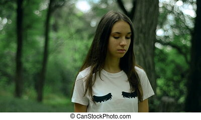young girl walks in the green forest