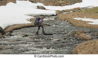 Young girl walks through the mountain river. Norway