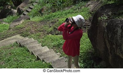 Young girl walks through tropical park and takes pictures of the beauty of nature stock footage video