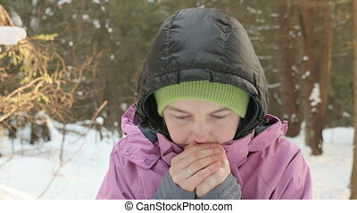 Young girl warms up the hands in the cold winter forest