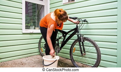Young Girl Washing The Bicycle Wheels
