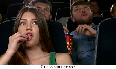Young girl watching movie at cinema: thriller, Close up -...