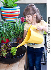 Young girl watering salad smiling