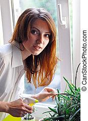 Young girl watering window plants