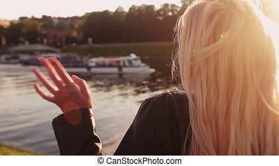 Young girl waves her hand a boat passing by the river. HD