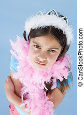 Young girl wearing crown and feather boa frowning