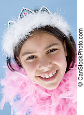 Young girl wearing crown and feather boa smiling