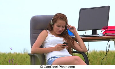 Young girl wearing headset during VoIP conversation and text...
