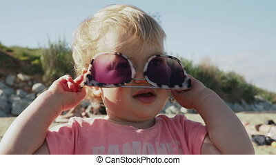 Young girl wearing large sunglasses on beach - Cute young ...