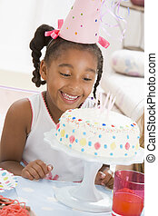 Young girl wearing party hat looking at cake smiling