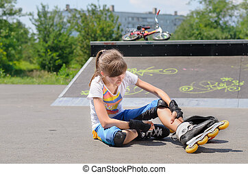 Young girl wearing rollerblades massaging her calf