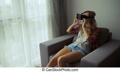Young girl wearing virtual reality goggles.