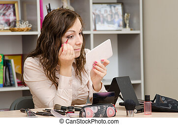 young girl wears a brush lashes at desk in office