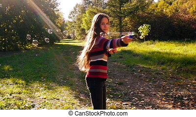 Young girl whirl with soap bubbles on autumn park, slow...