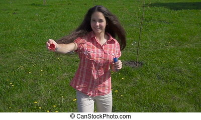 Young girl whirl with soap bubbles on spring park