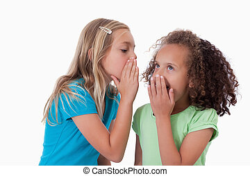 Young girl whispering a secret to her friend against a white...