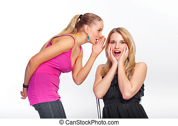 Young girl whispers a secret - A young girl whispers a...