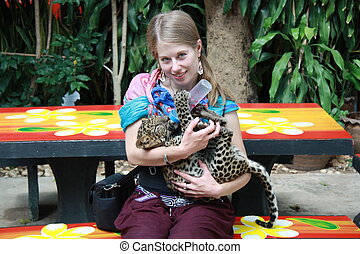Young girl with a baby leopard - Young Caucasian girl...