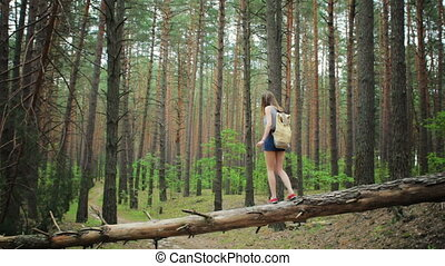 Young girl with a backpack in the woods