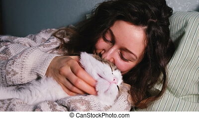 Young girl with a cat basking in bed