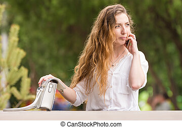 Young girl with a handbag talking on the phone