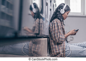 Young girl with a phone indoors