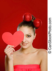 Young girl with a red heart toy in