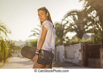 Young girl with a skateboard posing on the street