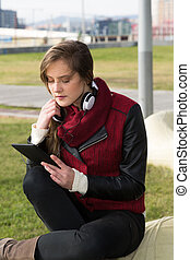 Young Girl with a tablet - Pretty girl listening to music on...