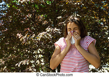 Young girl with allergy in autumn park. Sneezing girl blows her nose in a napkin