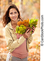 Young girl with autumn leaves in hand
