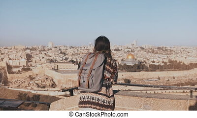 Young girl with backpack enjoys Jerusalem panorama. Thoughtful European tourist looks at ancient old town in Israel. 4K.