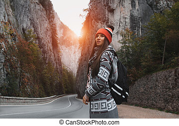 Young girl with backpack in mountains near the road.