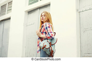Young girl with backpack walking in the city
