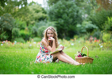 Young girl with bicycle, reading a book