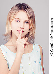 Young Girl with Blonde Bob Hairstyle. Teen Girl Holding her Finger to her Lips in a Gesture for a Secret