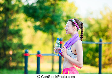 Young girl with botttle of water after running outside. Female fitness model training outside in the park. Concept of healthy and proper nutrition.