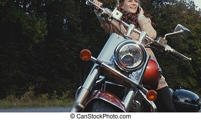 Young girl with brown hair sits on a motorbike near a road....