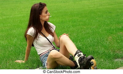 young girl with candy in mouth sitting on the grass in rollers
