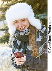 Young girl with cell phone in winter