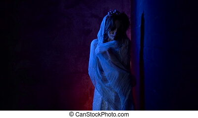 Young girl with creative halloween skull make-up is standing near the wall looking at the camera and wrapping herself in veil. Young woman with a carnival image of dead girl dressed in white costume is standing leaning against the wall with dark background behind her.
